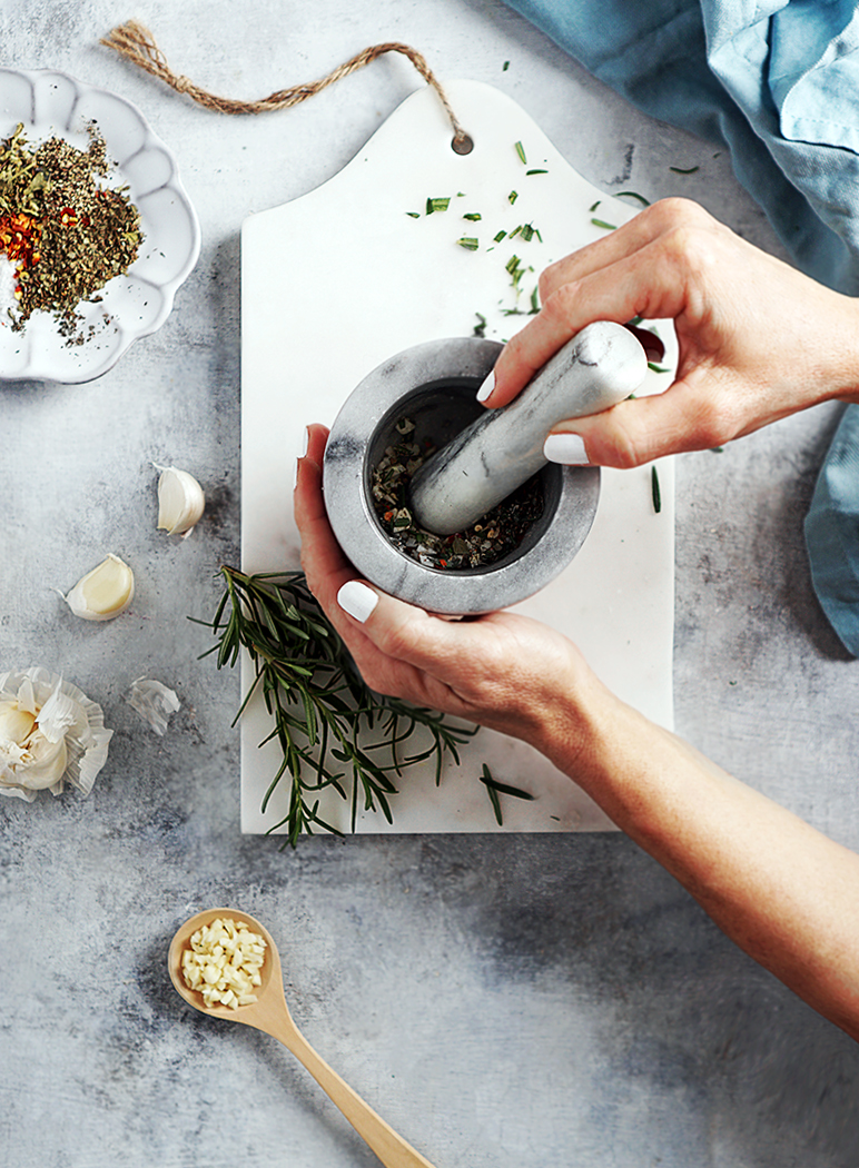two hands holding a mortar & pestle