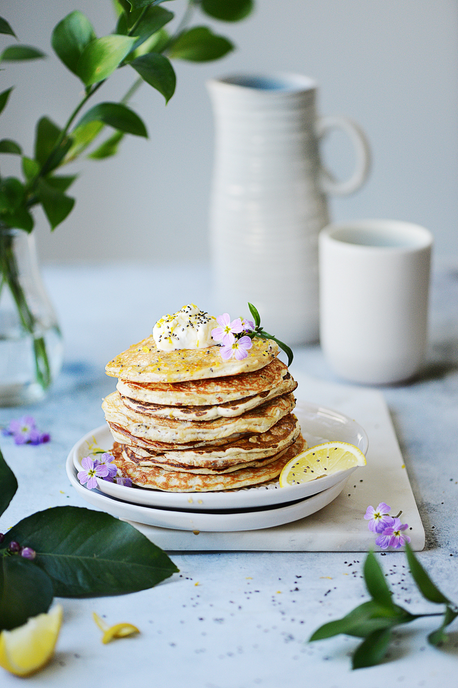 A stack of Lemon Pancakes on white plate with dripping syrup