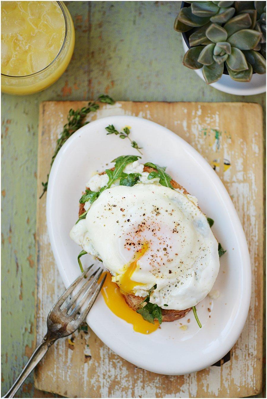 Egg on a toast with ricotta & arugula. Orange juice on the side
