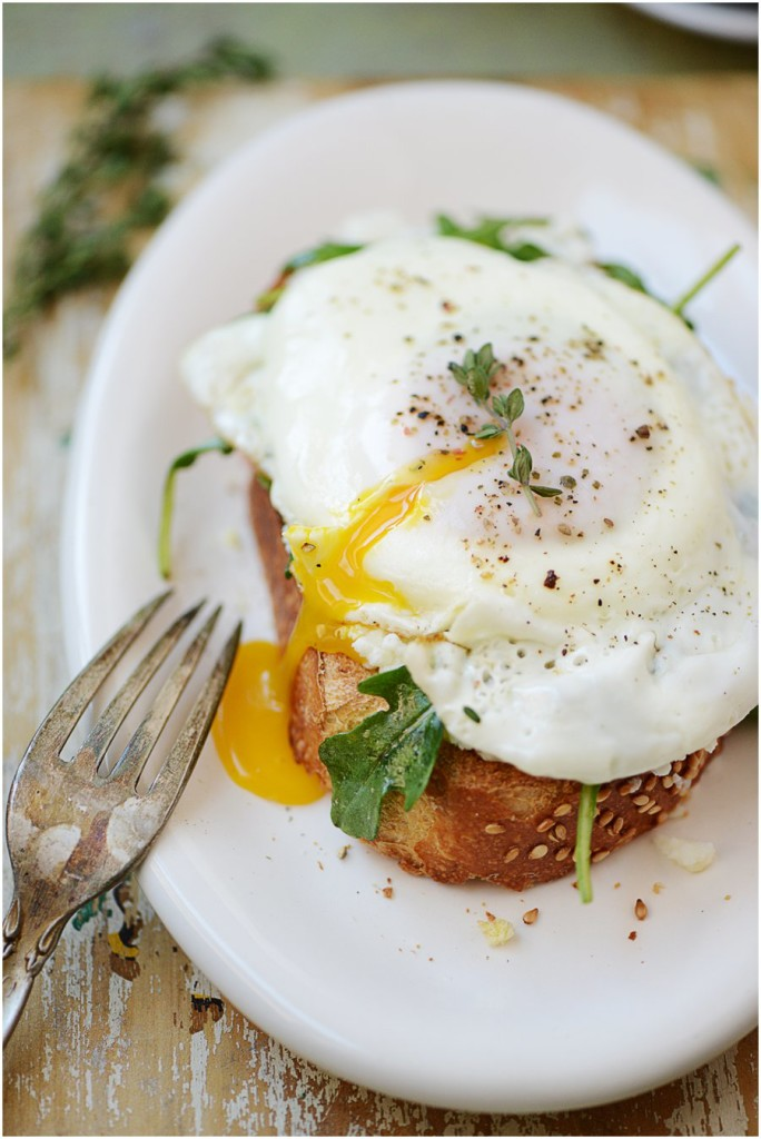 Egg on a toast with ricotta & arugula.