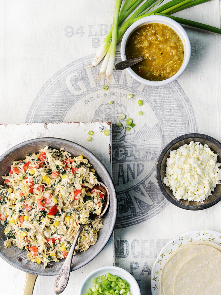 A skillet filled with shredded turkey two small bowls on the side