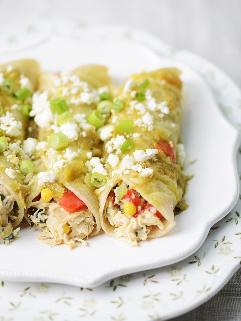 A close up photo of three enchiladas with green sauce