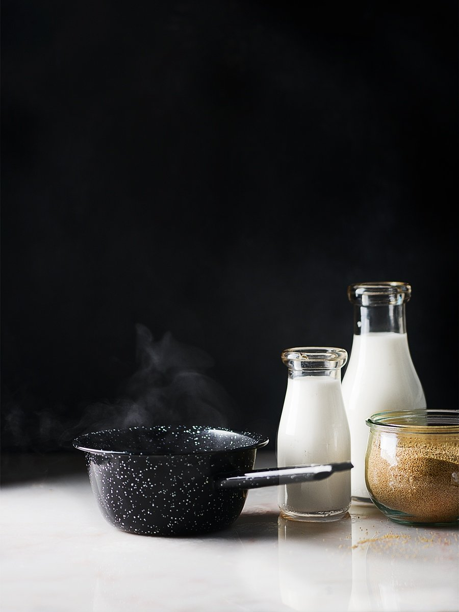 A steaming small pot with milk and ground oatmeal