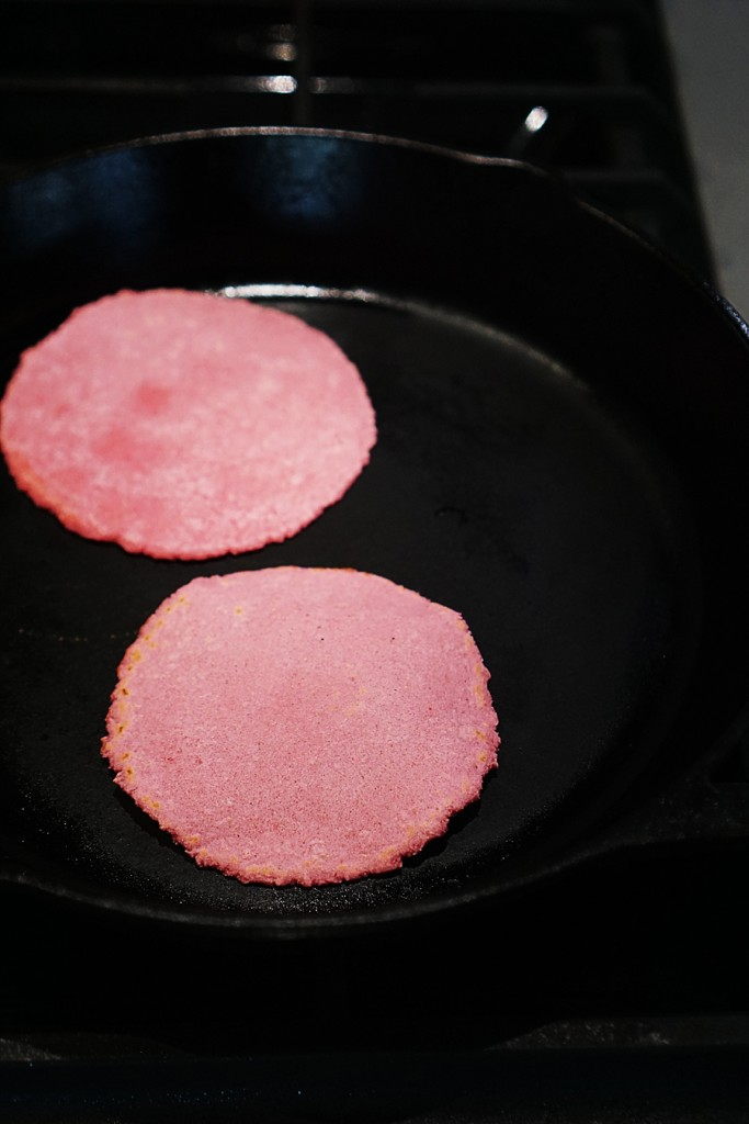 A iron skillet cooking two tortillas