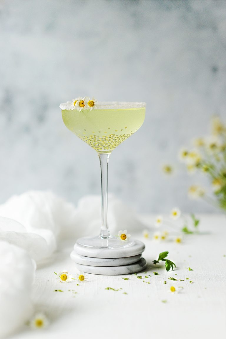 A tall cocktail glass with tequila sour garnished with chamomile flowers