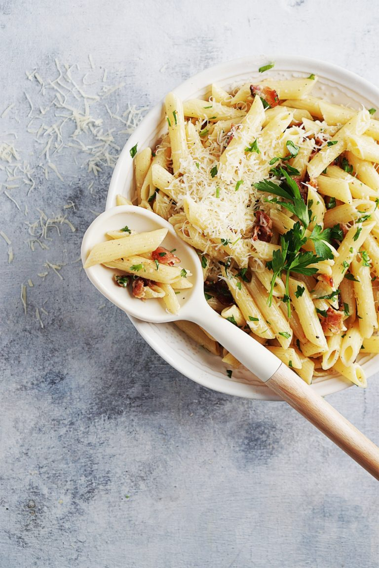 A bowl of pasta with bacon, parmesan cheese and herbs