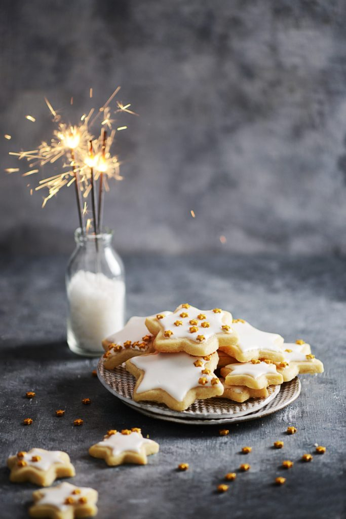 Cookies on a small plate and a sparkler in background. dark background photography