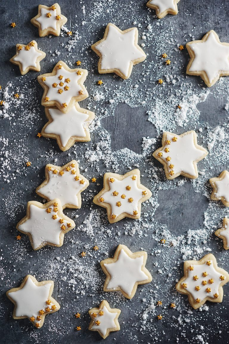 Sugar cookies in shape of stars on a gray backdrop