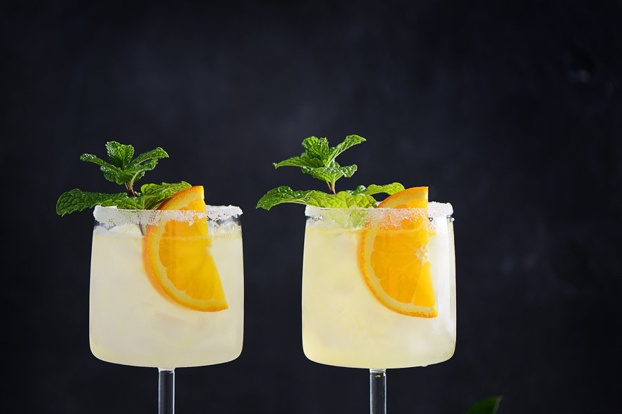 Vodka Collins Cocktail garnished with an orange