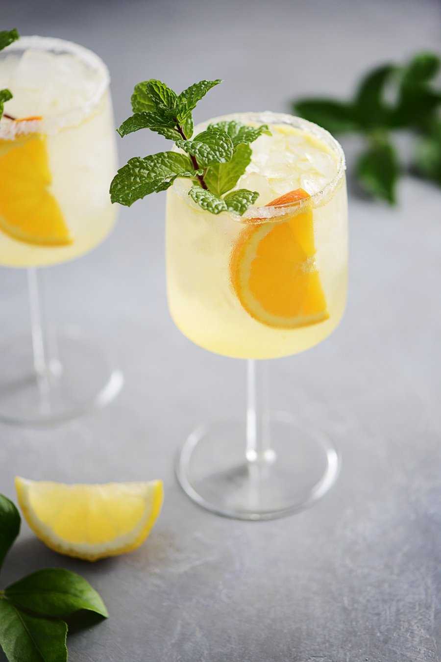 Vodka Collins Cocktail in two tall glasses garnished with an orange