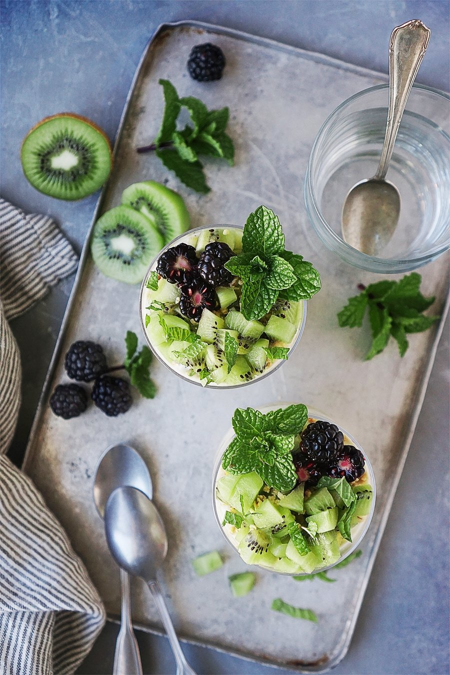 Two Yogurt Parfaits with sliced kiwis garnished with mint and blackberries