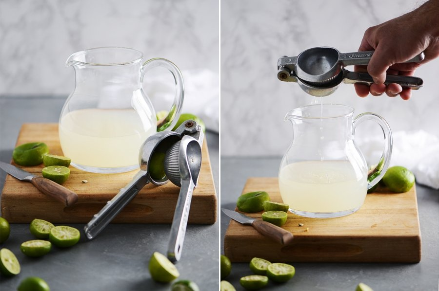 Preparation of lime margaritas with a jar of lime juice and squeezed limes around it. Lime juice squeezer on foreground.