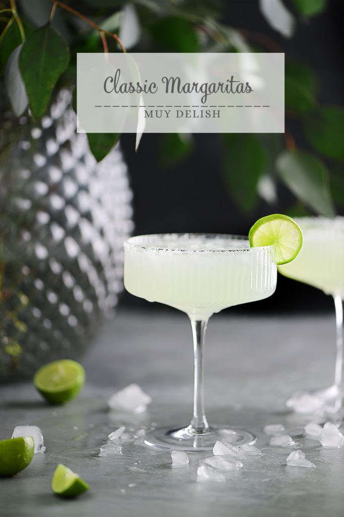 Margarita drinks garnished with limes. Vase with a plant on background.
