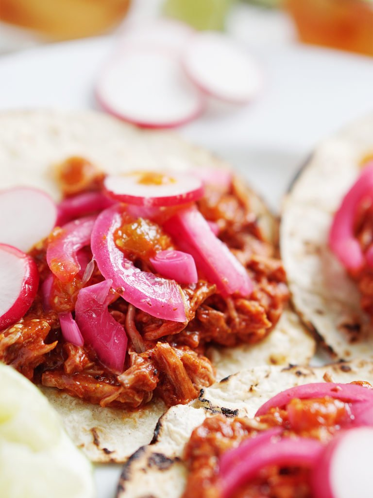 Cochinita Pibil Tacos on a plate with salsa and onions on the side. 3 drinks in glasses