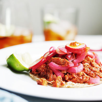 One Cochinita Pibil taco topped with picked onions and salsa. Lime on the side.