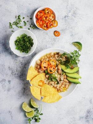 A bowl with Chicken Chili topped with tortilla chips and avocado. Cilantro and jalapeños on the side