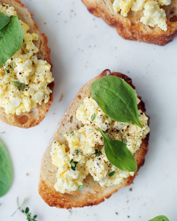 3 toast with egg salad on top with a few baby spinach leaves