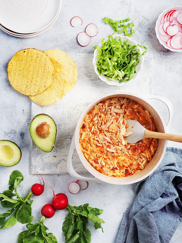 a medium size pot filled with chicken tinga. Tostadas on the side along with lettuce, radishes and an avocado
