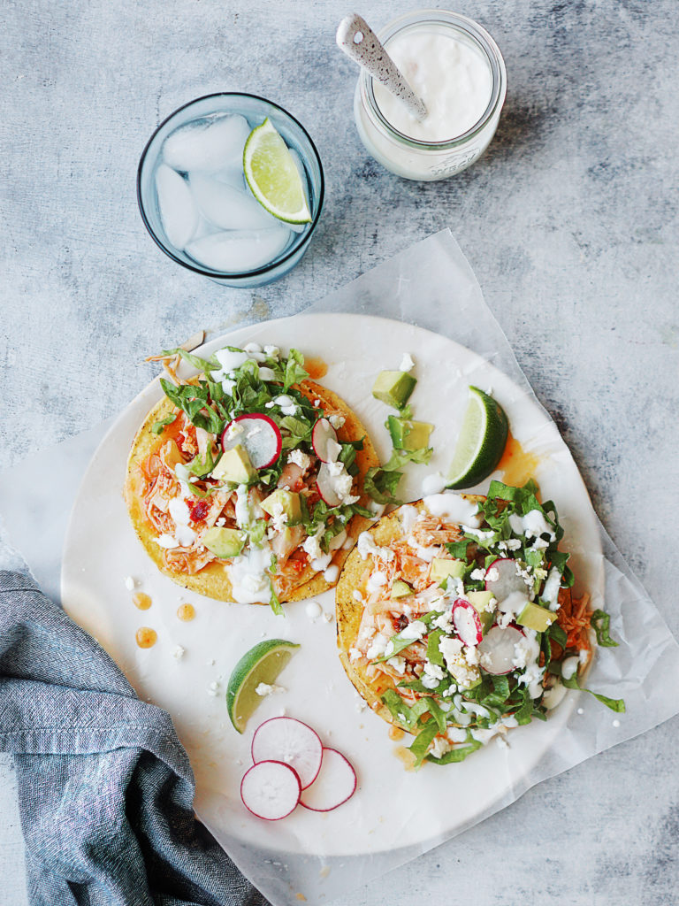 Two tostadas on a white plate with blue napkin on the side. A glass of water and crema on the side