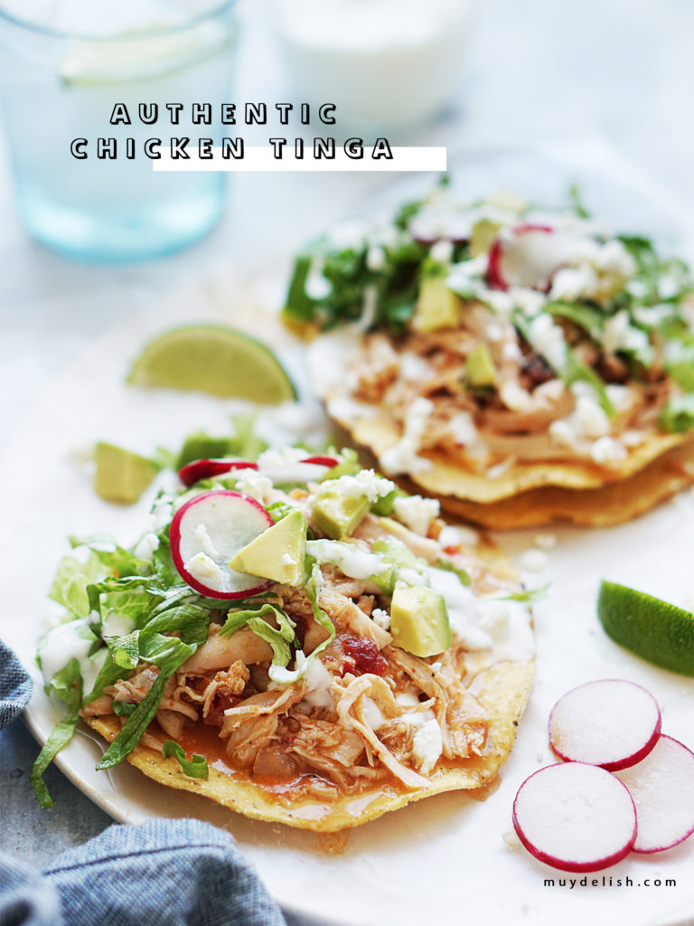 Two tostadas with shredded chicken and lettuce on top.