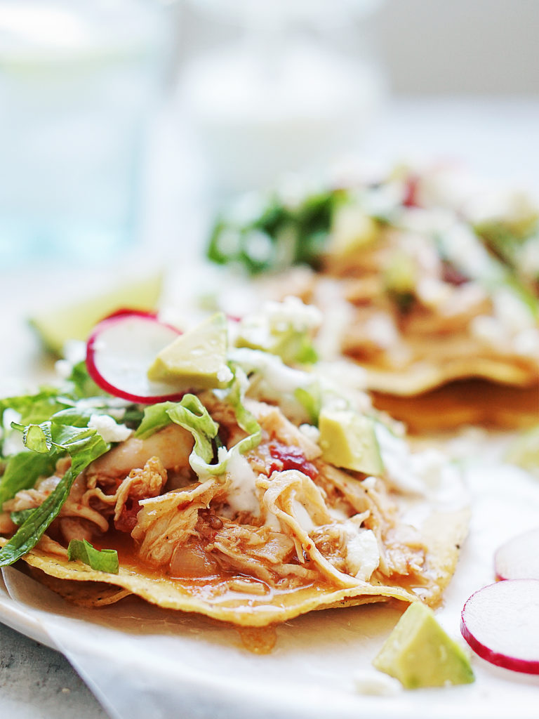 Close up photo of one tostada topped with chicken tinga, lettuce, and radishes