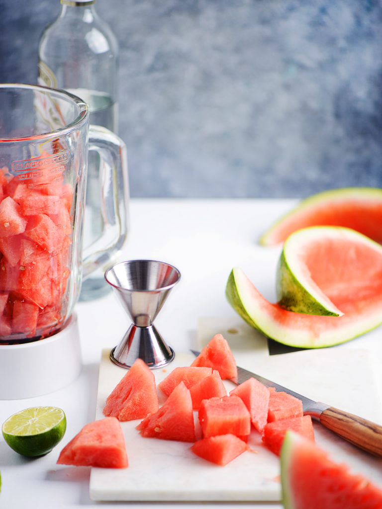 watermelon chunks with a blender on the side and a bottle of tequila in the background