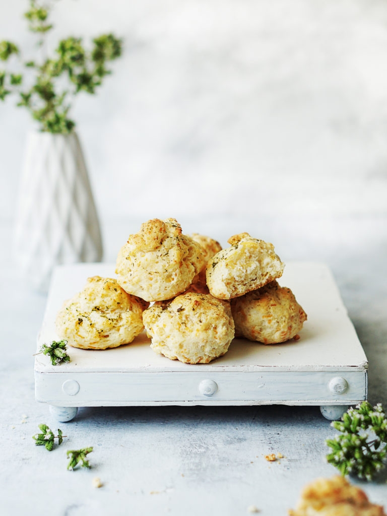 A small white board with 5 cheddar biscuits on top of it. One small white base with small white flowers in background