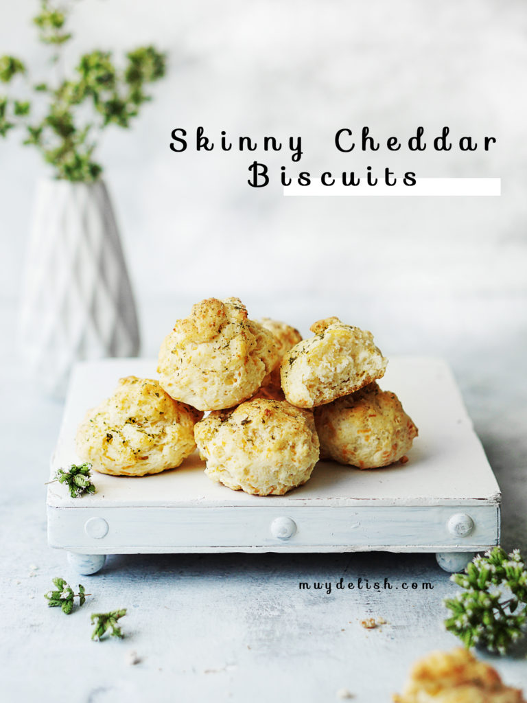 A small white board with 5 cheddar biscuits on top of it. One small white base with small white flowers in background .
