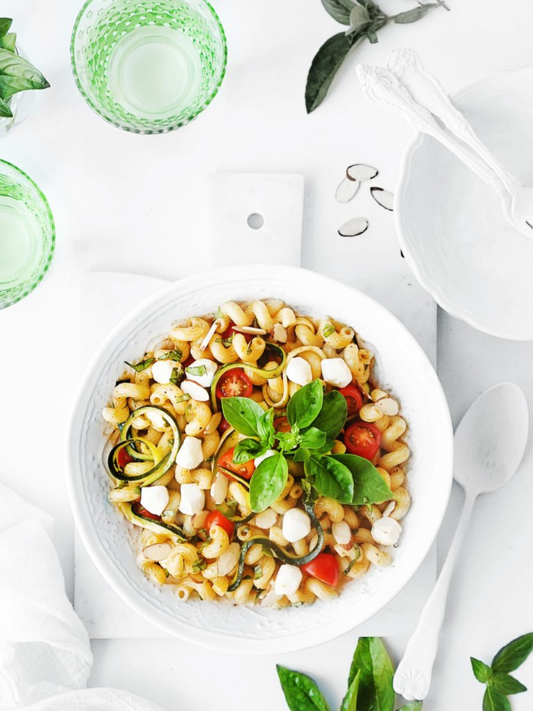 Overhead photo of a white bowl with pasta salad on a white background