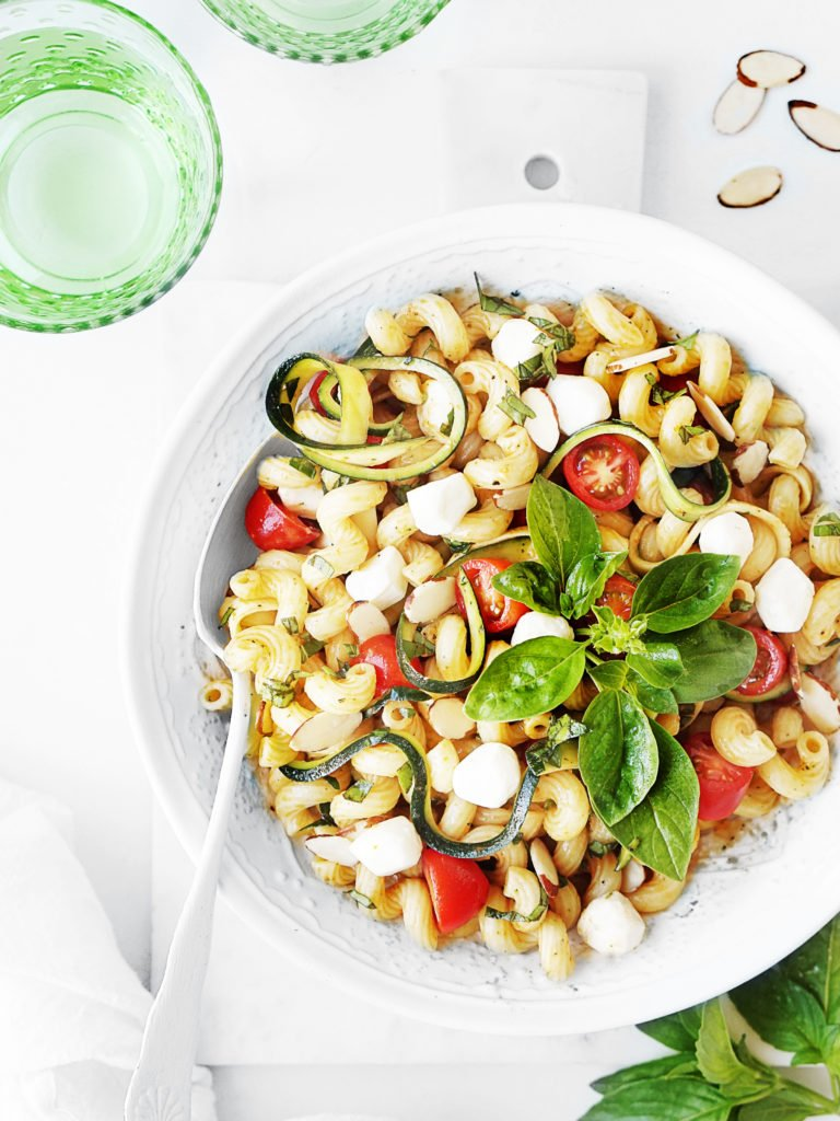 A white bowl with summer pasta salad and two green glasses with water on the side