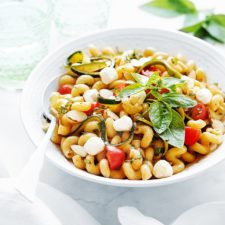 A bowl with pasta salad. Two serving bowls in foreground