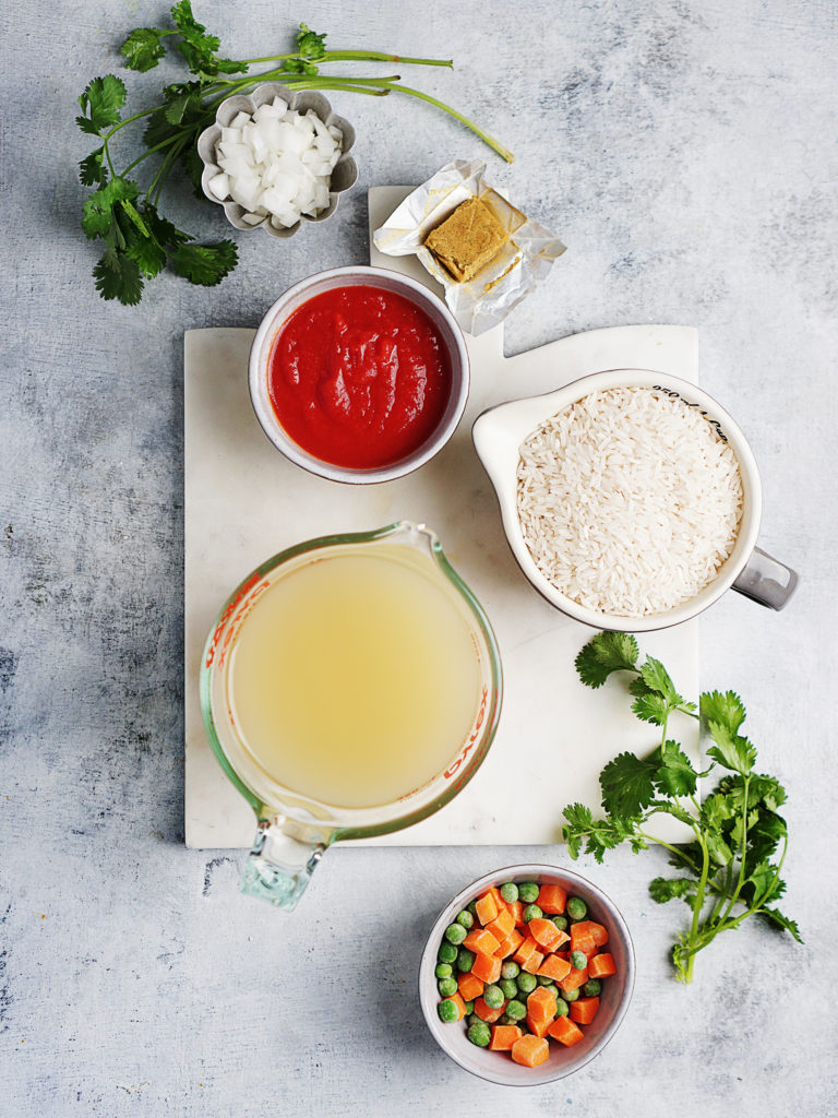 Ingredients photo in cups: white rice, stock, tomato sauce, frozen peas & carrots, onions and a bunch of cilantro