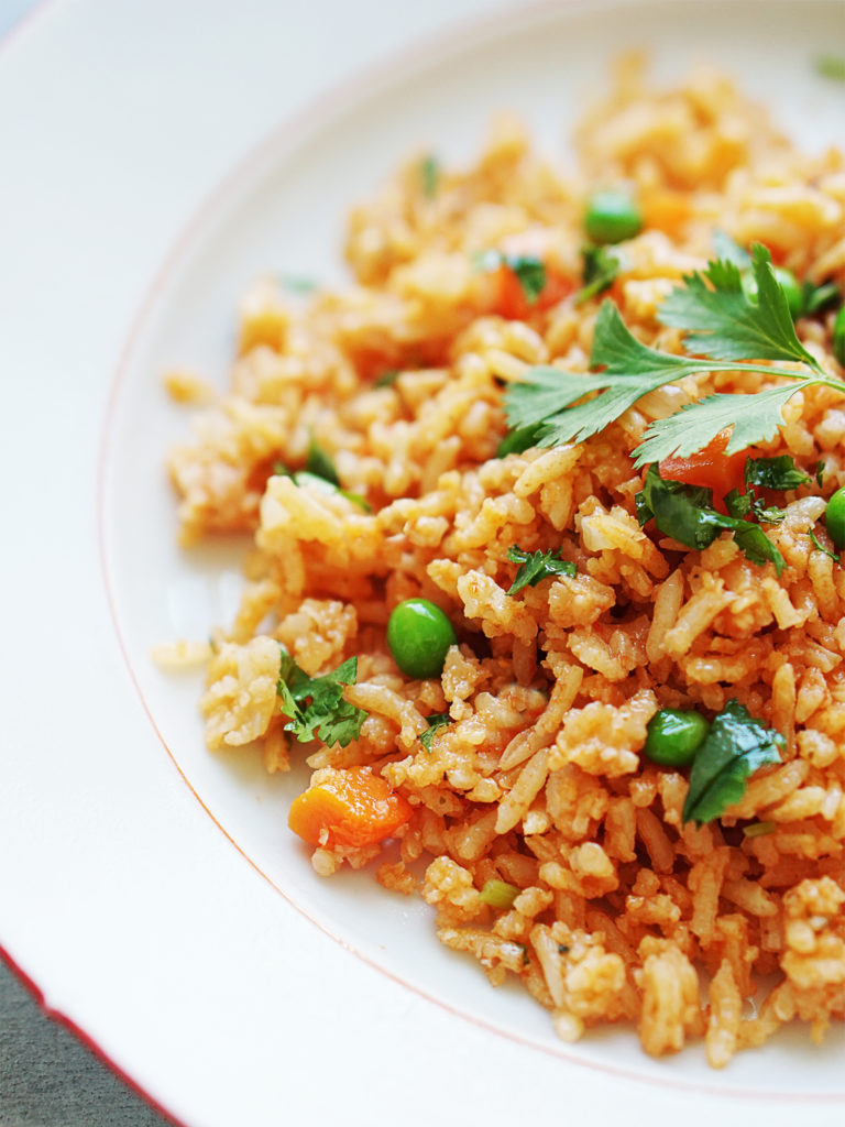 A close up photo of arroz Mexicano with peas & carrots
