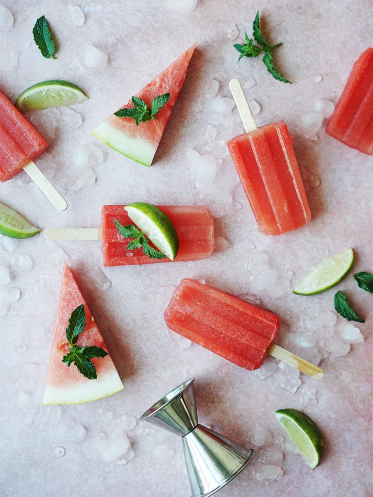 watermelons and boozy popsicles scattered on a pink background