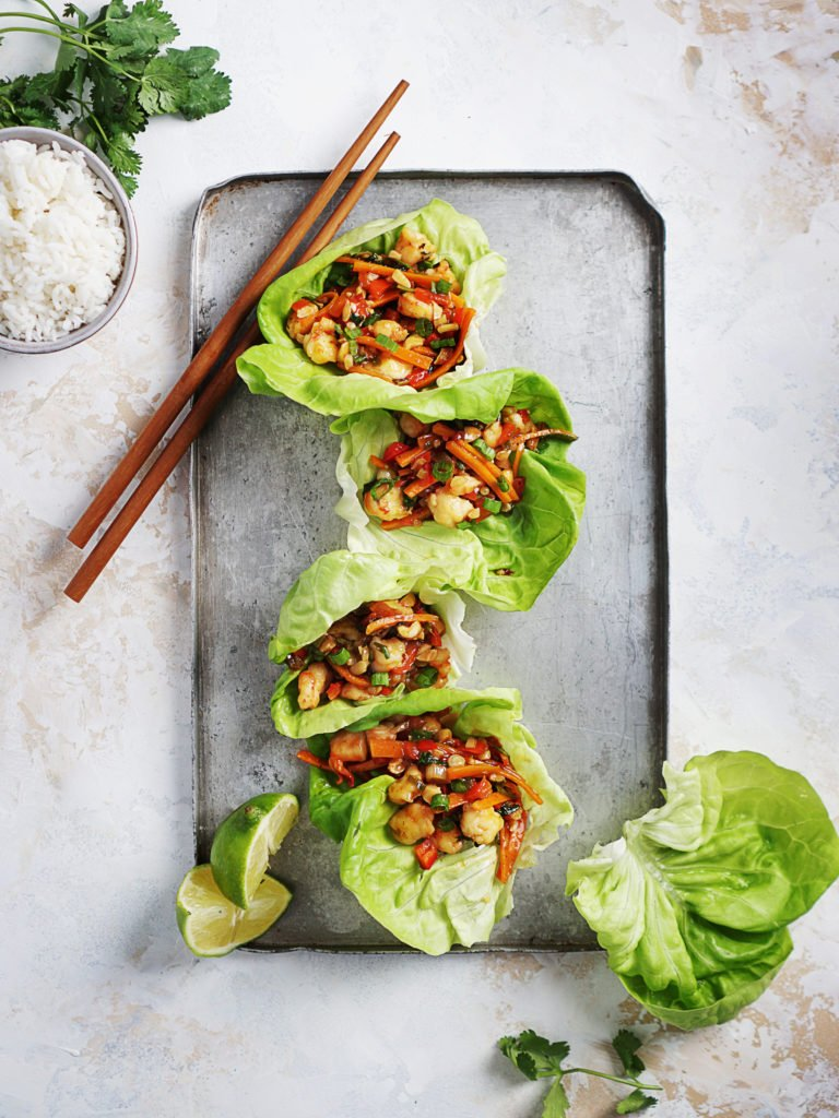 Four lettuce wraps on top of a metal tray.