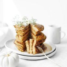 A stack of Protein Pumpkin Pancakes set on a table with a white tablecloth
