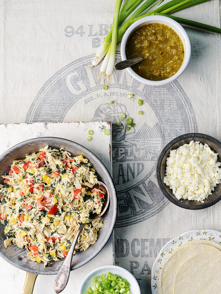 A skillet with shredded turkey in a creamy sauce. Tortillas, queso fresco and salsa on the side