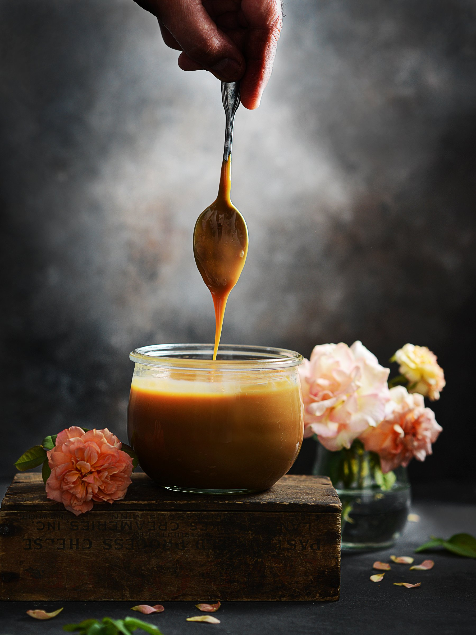 Moody food photography. A glass with Dulce De Leche with a spoon on top and dripping dulce de leche.