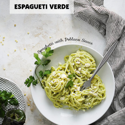 Espagueti Verde in a white bowl with a poblano pepper on the side