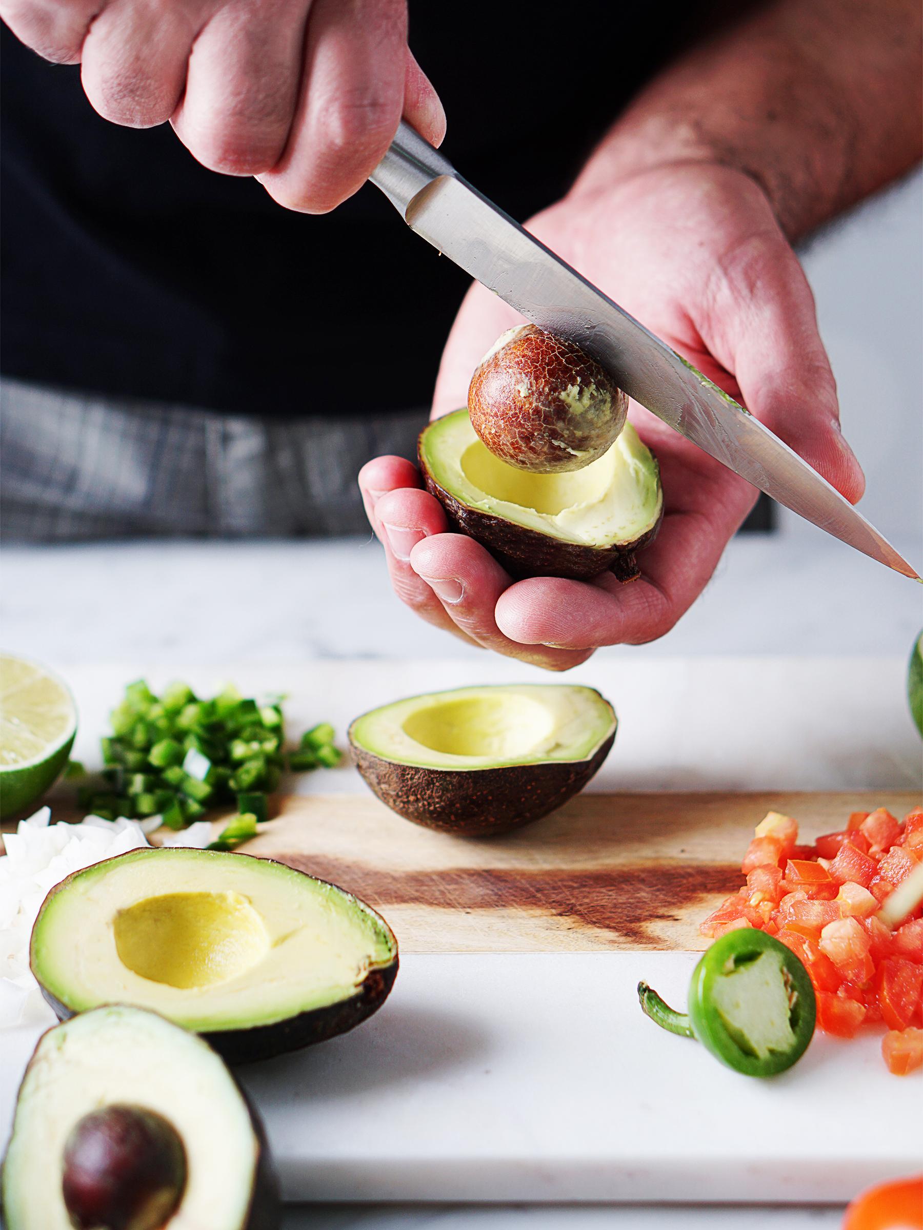 a man cutting an avocado