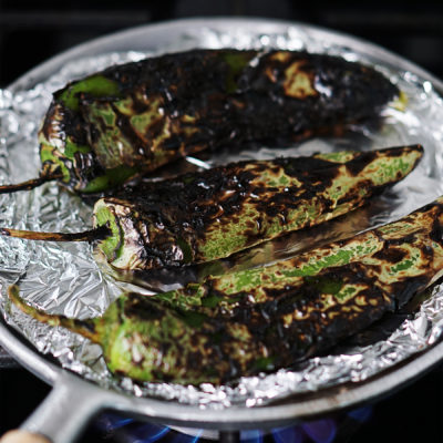 A griddle on top of a gas stove with charred peppers