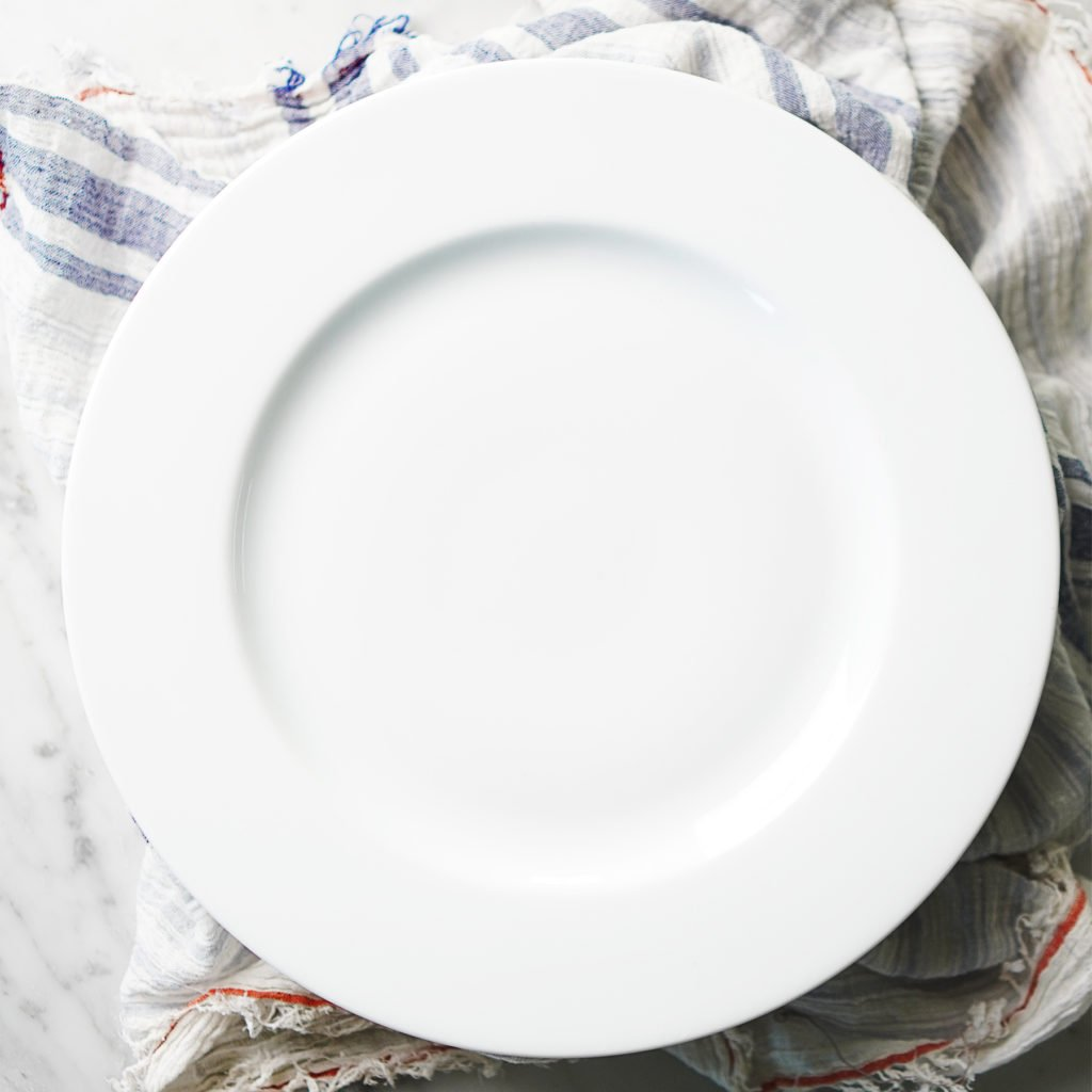 A white plate covering the bowl with roasted peppers