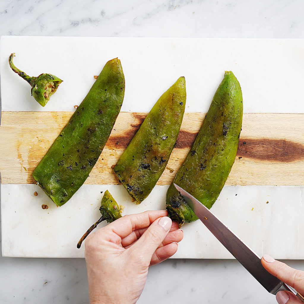 Cutting the tip of 3 Anaheim roasted peppers
