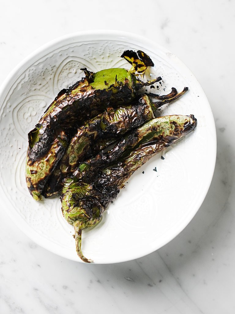3 roasted anaheim peppers in a white bowl