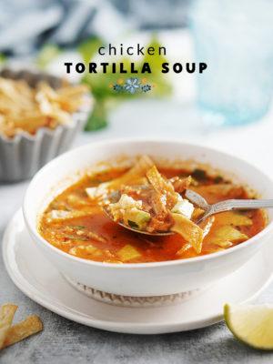 A white bowl of sopa de tortilla with a spoon