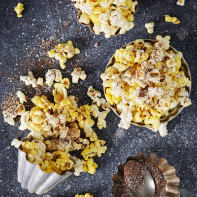 Palomitas (popcorn) scattered on a dark board with spices on a spoon