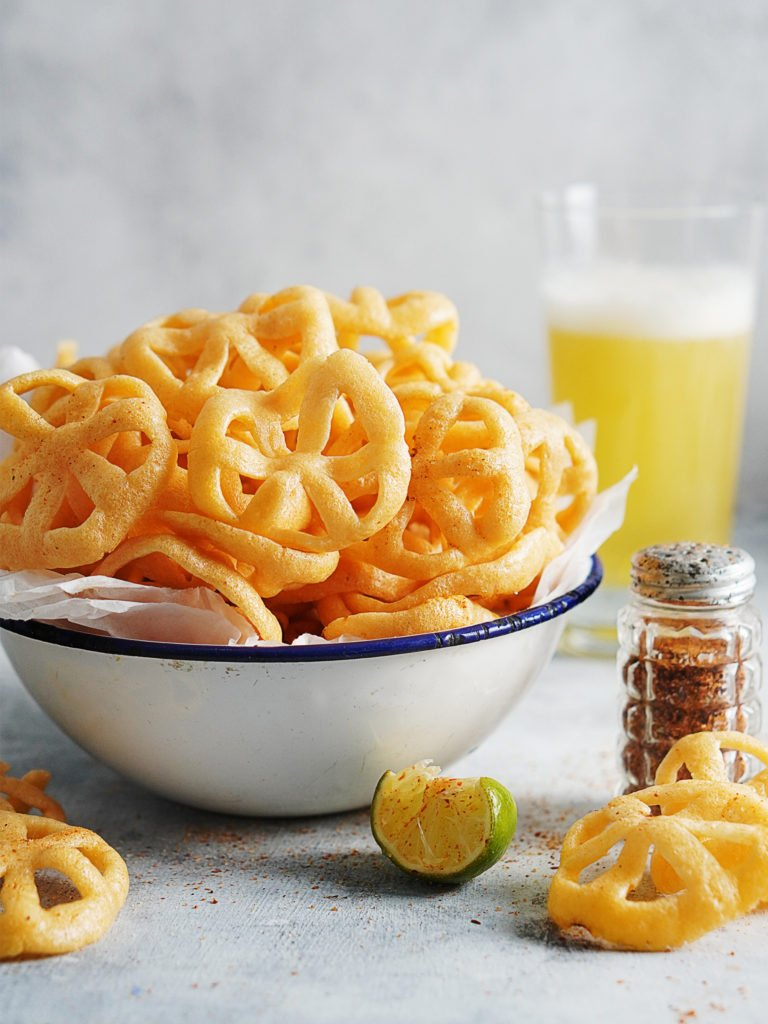 A bowl of chicharrones de harina with a lime on the side