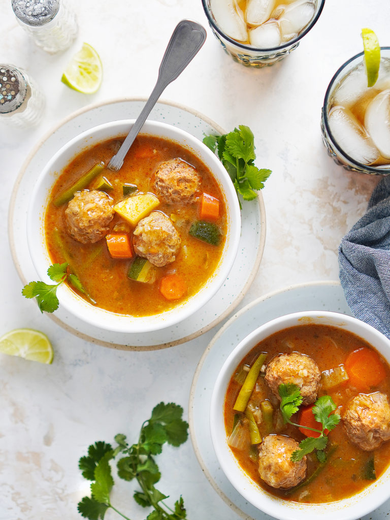Two white bowls with Caldo De Albondigas