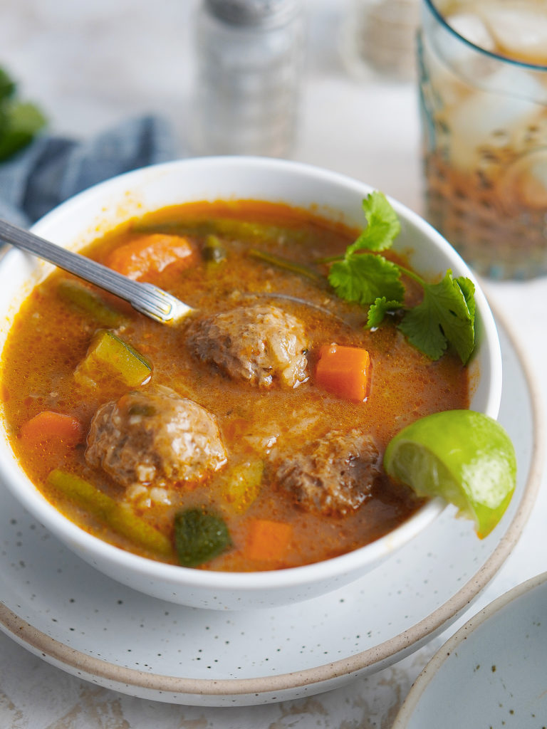 3 Mexican Albondigas in a white bowl with a lime on the side