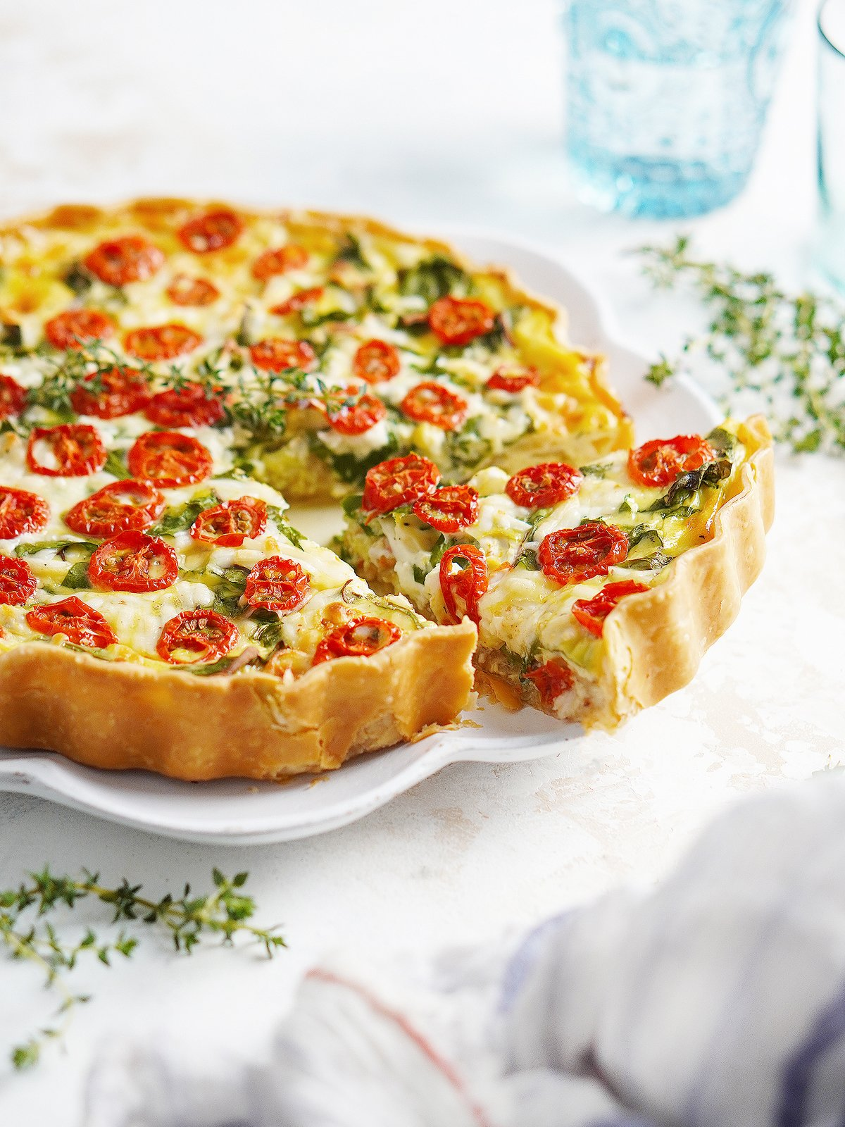 A quiche on a plate with a slice coming out